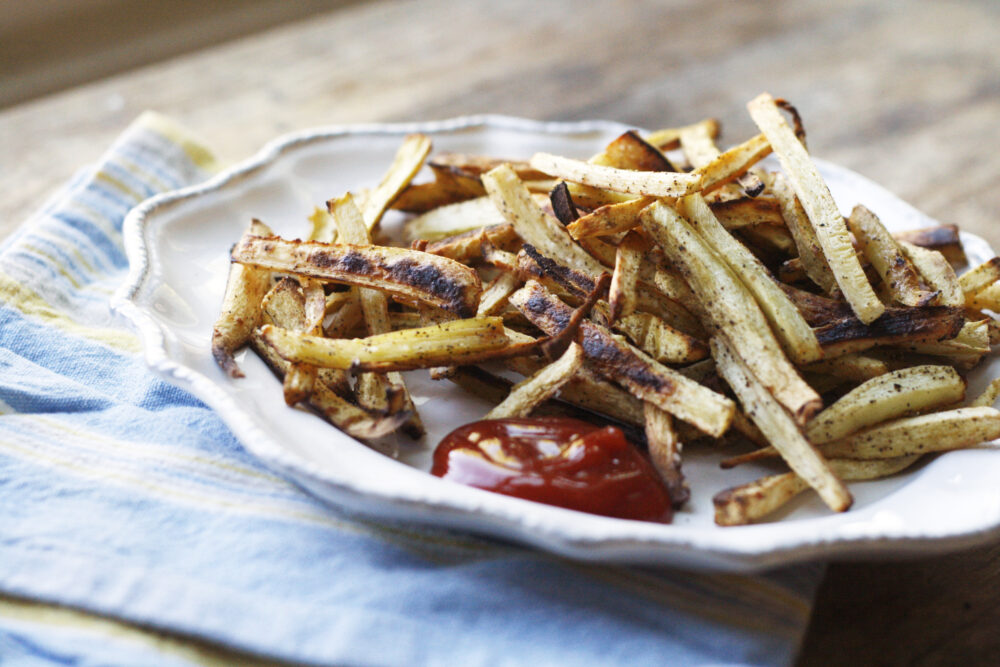 Baked Peppery Parsnip Fries are shown on a white plate atop a blue and yellow napkin on a wood surface.