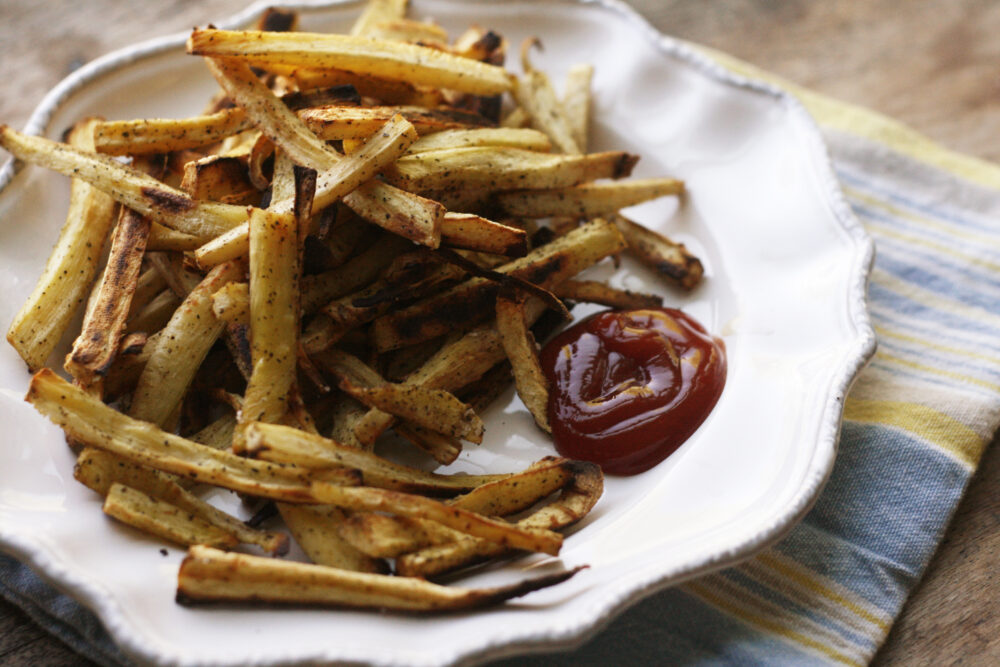 a plate of Baked Peppery Parsnip Fries with ketchup is shown on a blue and yellow napkin.