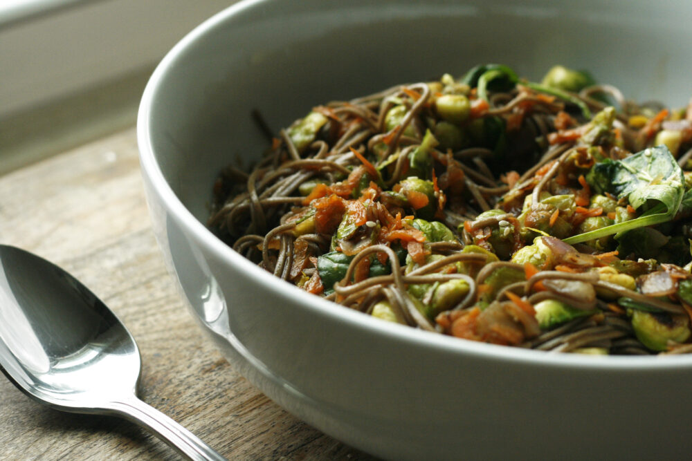 Sesame Soba Noodles with Brussels Sprouts in a white bowl on a distressed wooden table.