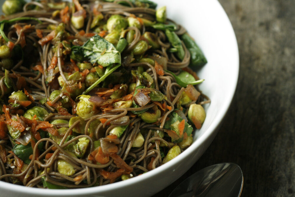 Sesame Soba Noodles with Brussels Sprouts is shown in a white bowl on a wooden table.