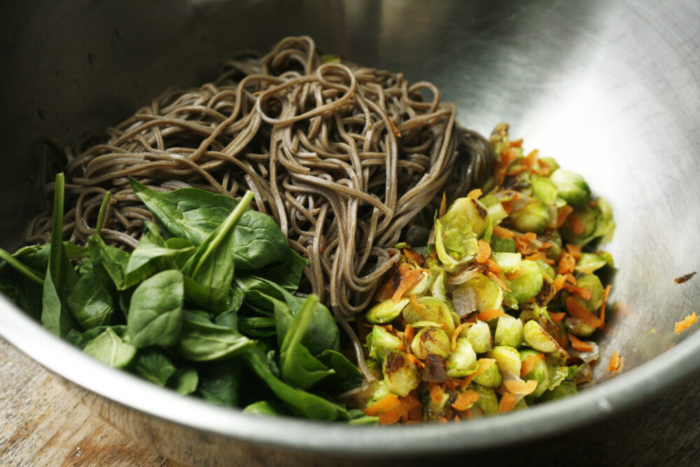 Sesame Soba Noodles with Brussels Sprouts in progress shown in a silver bowl.