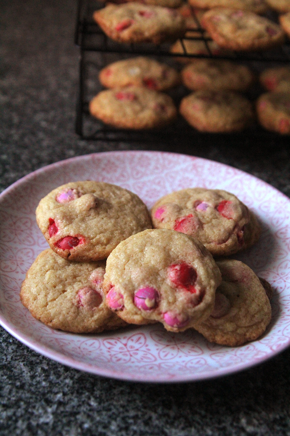 A pink and white plate on a granite countertop shows a pile of M&M cookies for Valentine's Day dotted with red and pink candies. A cooling rack with cookies sits in the background.