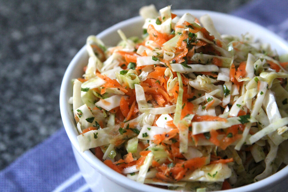 Easy Oil and Vinegar Coleslaw is shown in a white bowl on a blue towel on a gray granite countertop.