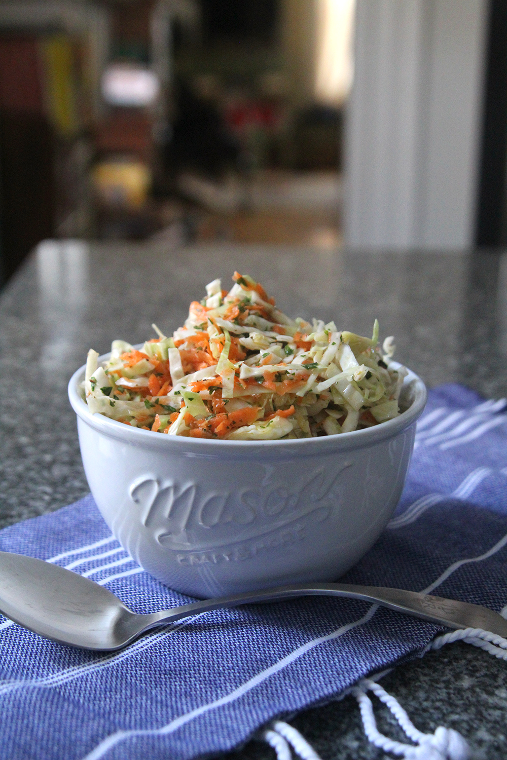 Oil and Vinegar Coleslaw is shown in a white bowl on a blue and white cloth on a granite countertop with a silver spoon nearby.