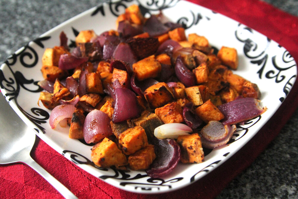 Roasted Sweet Potatoes and Red Onions with Gochujang Seasoning recipe is shown on a black and white plate on top of a red napkin on a granite countertop.