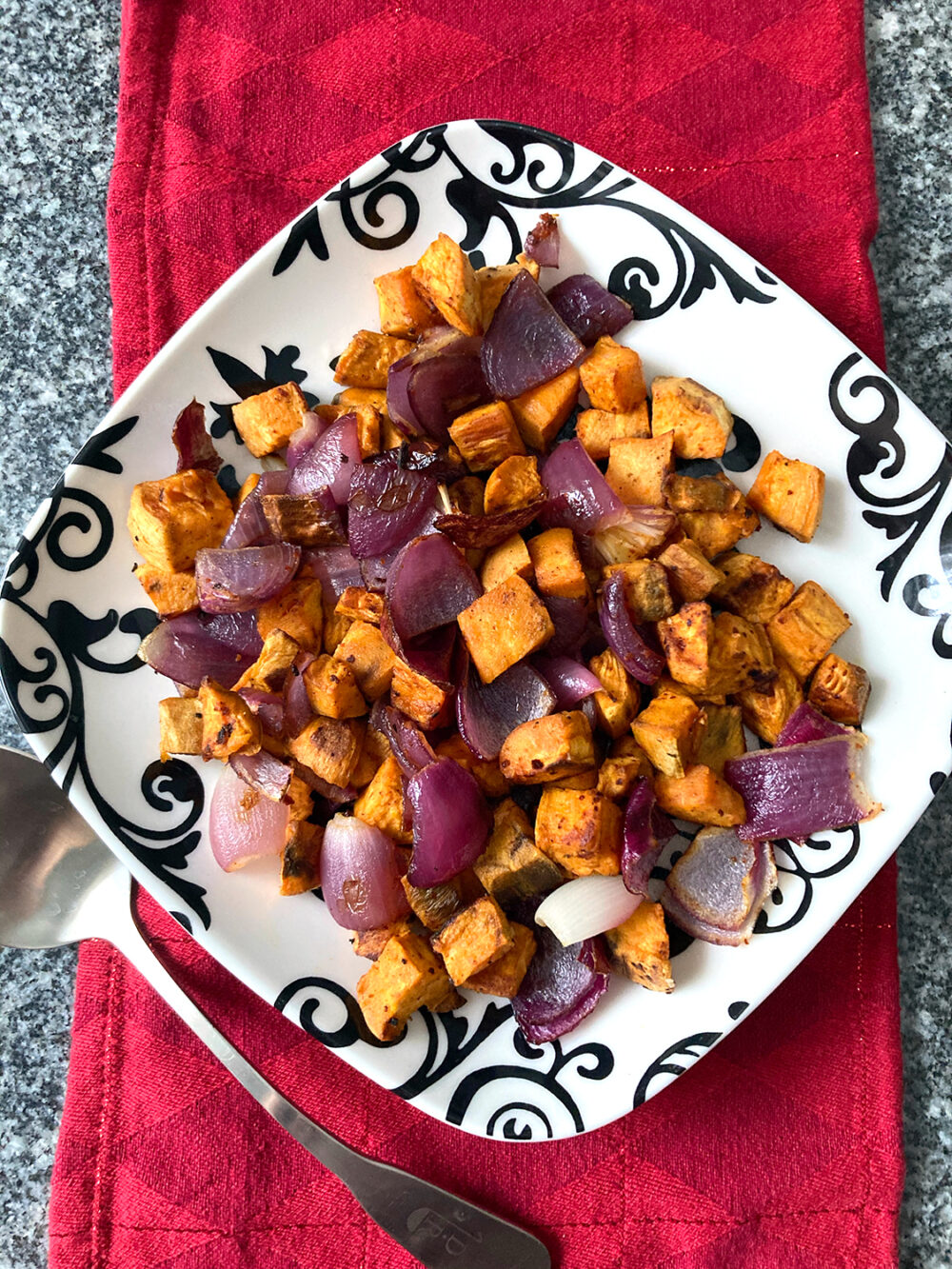 An overhead shot of Roasted Sweet Potatoes and Red Onions with Gochujang Seasoning recipe on a black and white plate on a red napkin on a granite countertop.