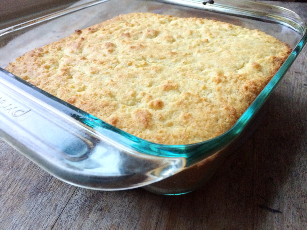 A glass pan of Buttery Cornbread is shown from the side on a wooden countertop.
