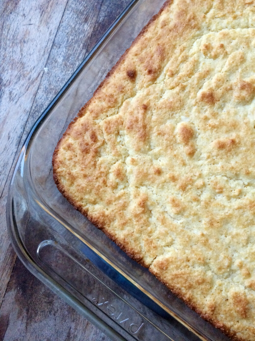 A glass pan of Buttery Cornbread is shown on a wooden countertop.