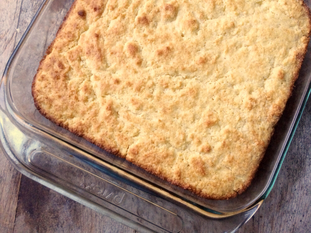 A glass pan of Buttery Cornbread is shown from above on a wooden countertop.