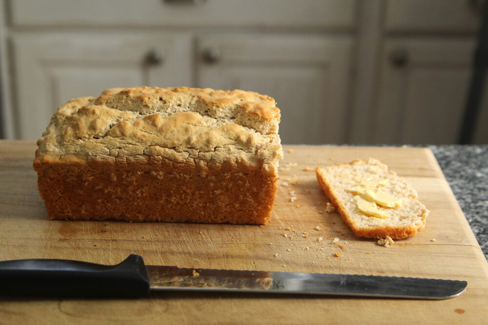 A loaf of easy beer bread is shown in a cutting board. A knife and one buttered slice sit nearby.