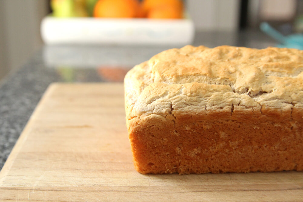 A loaf of golden brown bread sits on a cutting board on a granite countertop.
