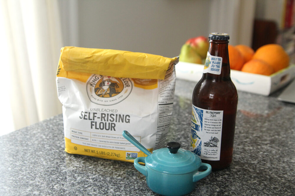 Easy Beer Bread is made with three ingredients pictured here: self-rising flour, beer and salt. These are shown on a granite countertop with a tray of fruit in the background.