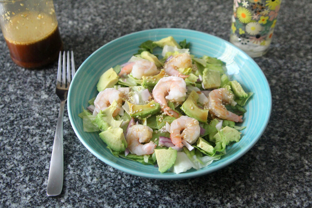 A salad featuring shrimp, avocado and red onions dressed with Sesame Ginger Dressing sits on a granite countertop with a fork, more dressing and a glass of water nearby.