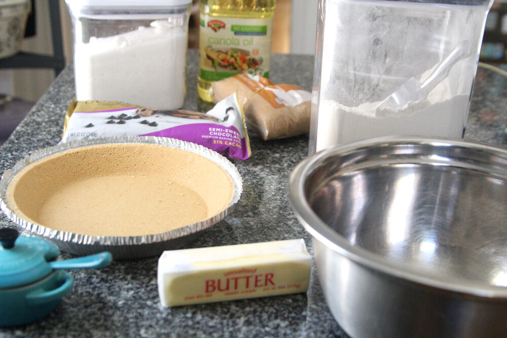 Ingredients for Chocolate Chip Pie are shown on a granite countertop including butter, a pie shell, chocolate chips, white sugar, brown sugar, canola oil and flour.