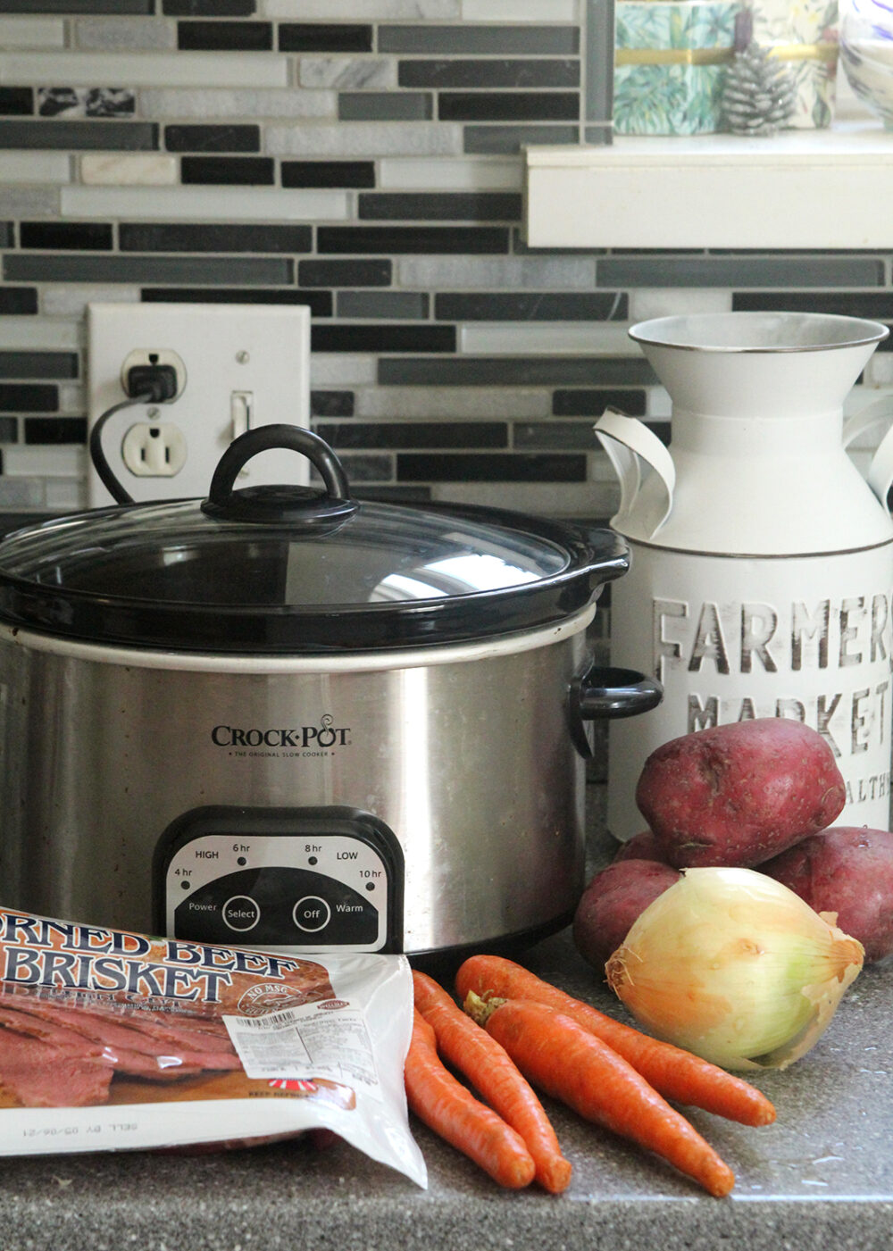 A Crock-Pot, potatoes, carrots, an onion and a package of corned beef sit on a counter.