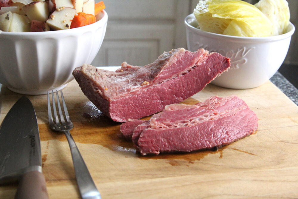 Corned beef is shown on a wooden cutting board with a bowl of potatoes and carrots, a bowl of cabbage and a fork and knife nearby.