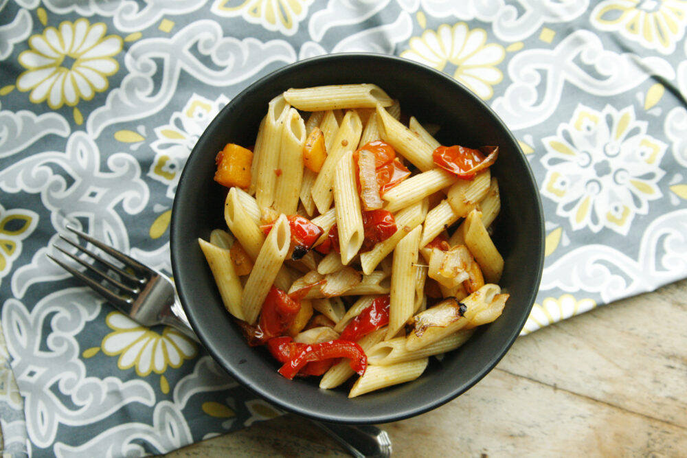Penne pasta is combined with roasted peppers, butternut squash and onions in this Roasted Vegetable Pasta Toss recipe. Here it's shown in a black bowl on a grey, white and yellow mat with a fork nearby.