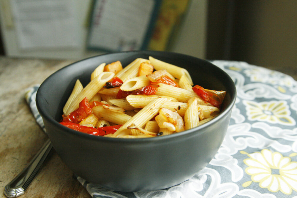 A bowl of Roasted Vegetable Pasta Toss featuring red peppers and penne pasta sits on a grey, yellow and white mat on a wooden table with a fork nearby.
