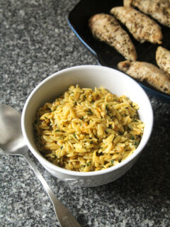 A bowl of lemon butter orzo sits on a counter next to a pan of chicken and a silver serving spoon.