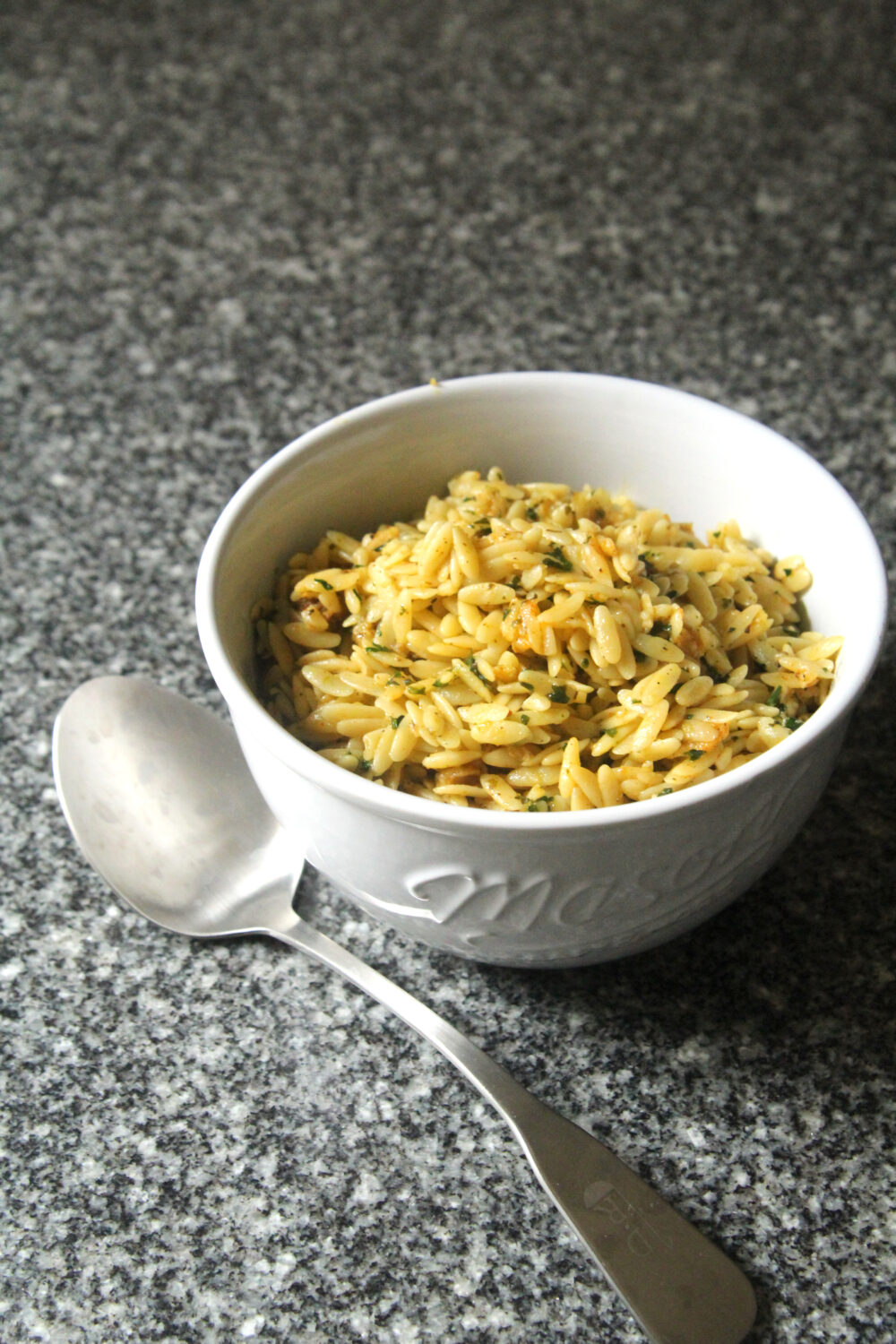 A white bowl holds yellow-ish lemon butter orzo on a granite countertop. A silver serving spoon sits nearby.