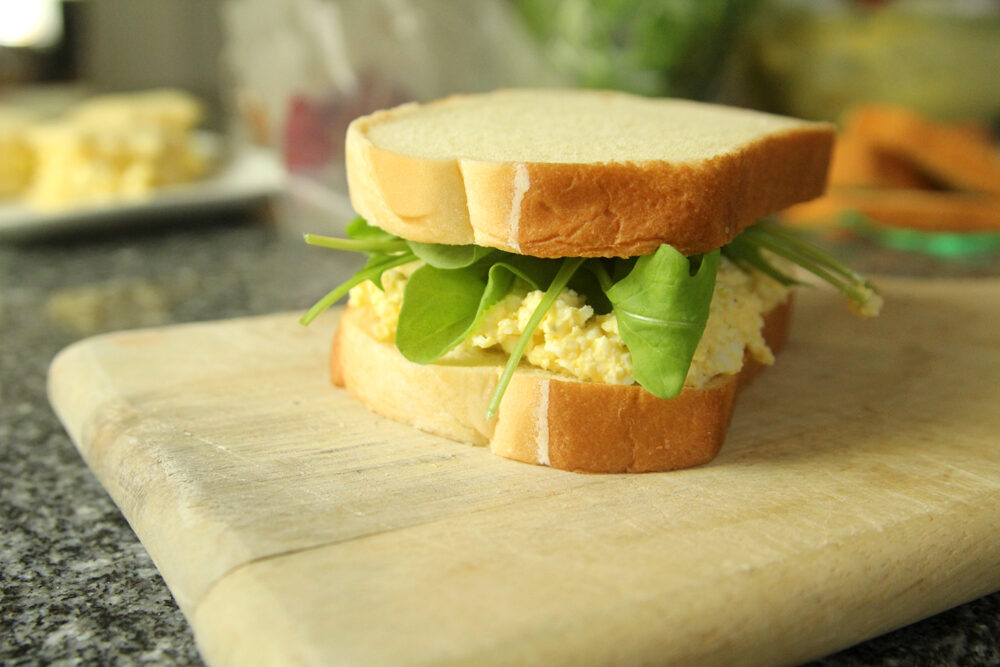An egg salad sandwich on potato bread with green arugula poking out is shown on a wooden cutting board.
