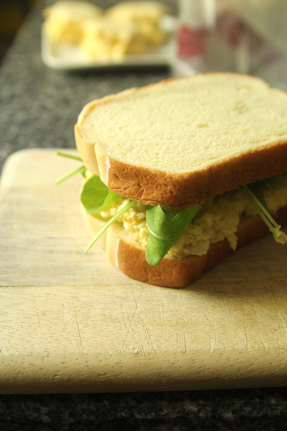 A sandwich made with egg salad is shown on a cutting board. Green baby arugula pokes out in all directions.