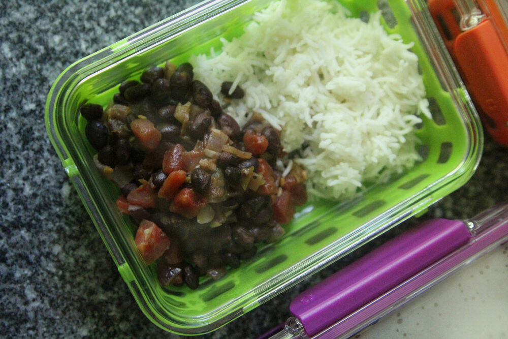 Steaming black beans with tomatoes and onions are shown with white rice in a green meal prep container.