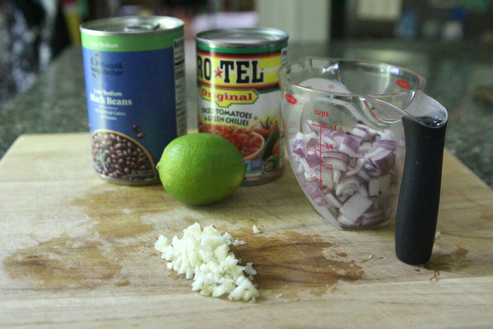 On a cutting board, a can of black beans, diced tomatoes with green chilies, a lime, diced red onion and minced garlic sit.