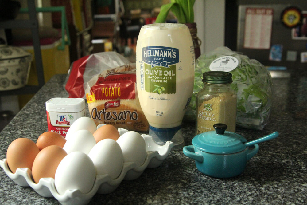 Ingredients for this easy egg salad recipe are shown on a granite countertop. They include eggs, salt, pepper, mustard, mayonnaise, bread and arugula.