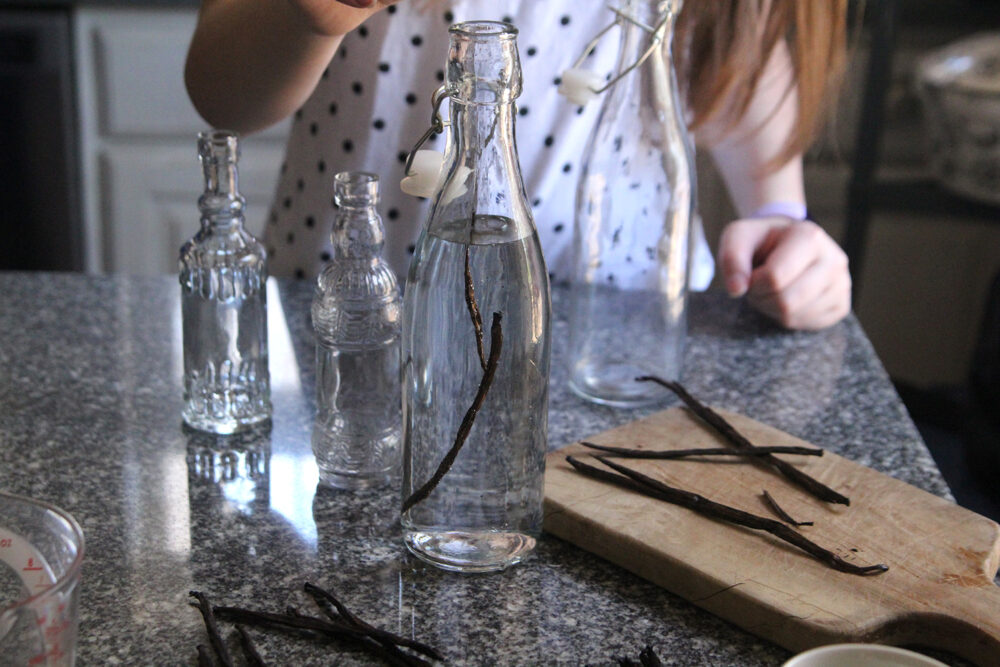 Vanilla beans are seen being placed into a bottle filled with clear liquid. Other vanilla beans sit nearby on the counter and on a cutting board.