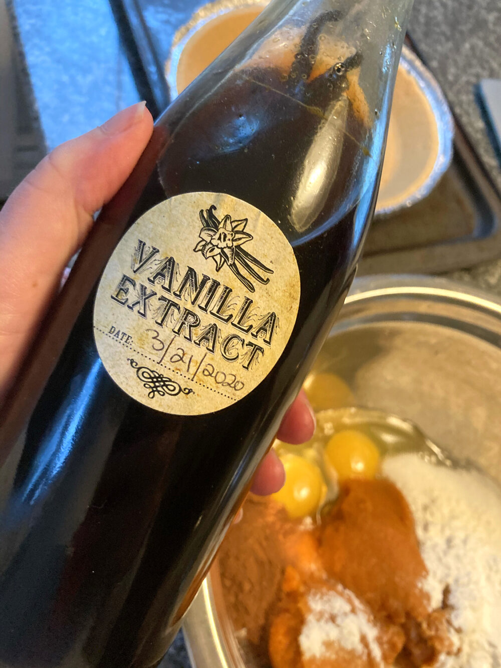 A bottle of homemade vanilla extract with vodka is held in a hand over a counter with a pie plate and batter. The extract is a dark, rich brown and the vanilla beans can be seen poking out of the liquid.