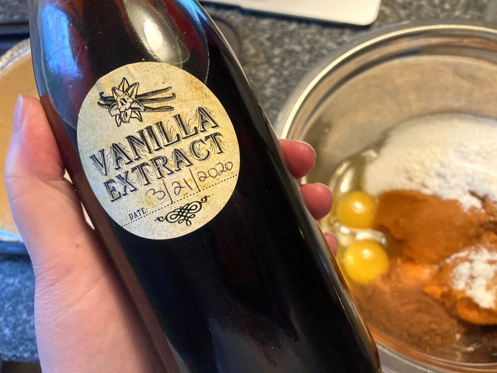A bottle of vanilla extract is held in a hand over a mixing bowl.