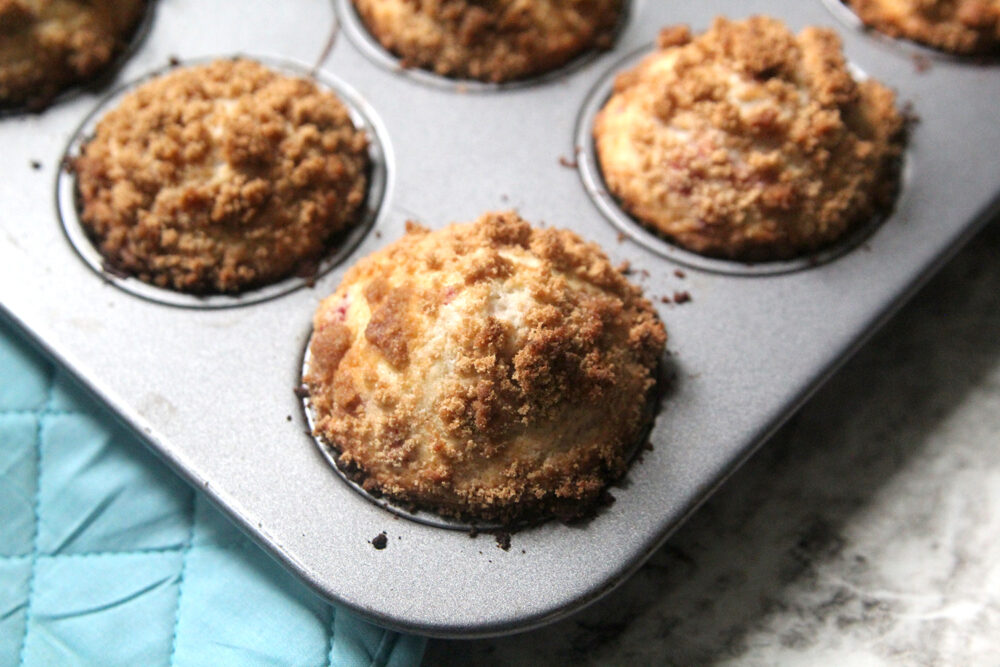 Raspberry Streusel Muffins sit in a muffin pan on a counter, hot from the oven.
