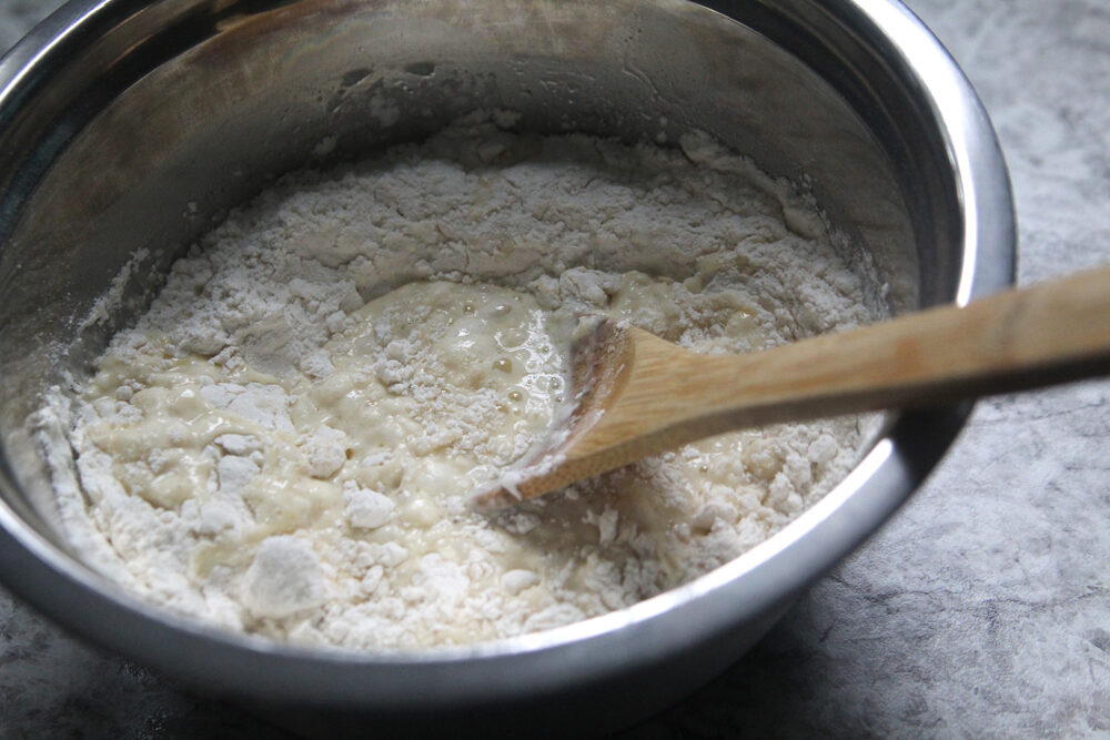 A silver bowl holds partially mixed batter with a wooden spoon.