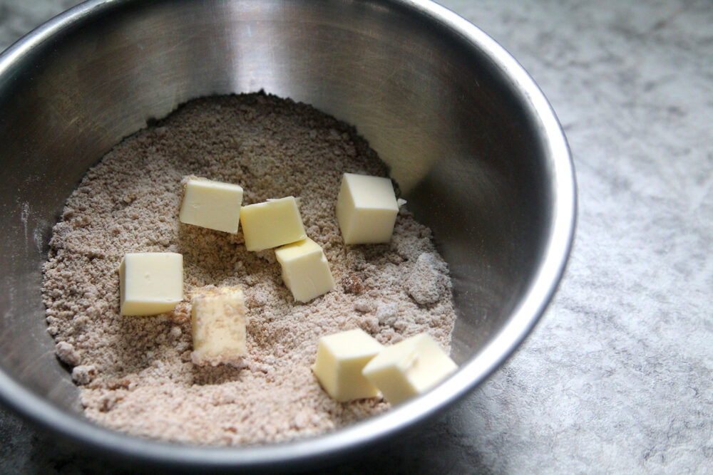 A silver bowl holds a beige mixture with cubes of butter on top.